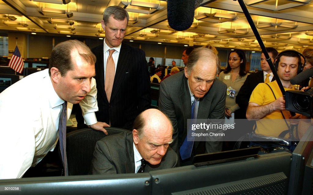 U.S. Treasury Secretary John Snow (C, seated) views a computer screen as Tom Conner (L), JP Morgan head of treasury and agency bond trading, explains data on the JP Morgan trading floor February 24, 2004 in New York City. Snow said the U.S. economy is performing well and said a team of U.S. Treasury officials is heading to China to address currency exchange rates there.