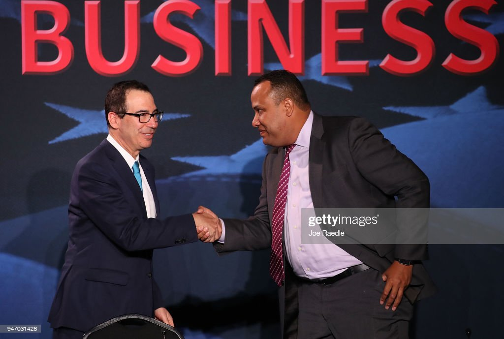Treasury Secretary Steven Mnuchin greets Jose Mallea before a roundtable discussion with President Donald Trump about the Republican $1.5 trillion tax cut package he recently signed into law on April 16, 2018 in Hialeah, Florida. Trump was joined by local business owners Labor Secretary Alex Acosta and others.