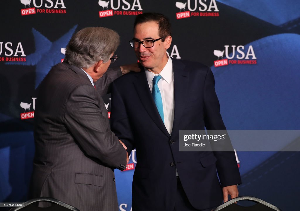 Treasury Secretary Steven Mnuchin greets Maximo Alvarez before a roundtable discussion with President Donald Trump about the Republican $1.5 trillion tax cut package he recently signed into law on April 16, 2018 in Hialeah, Florida. Trump was joined by local business owners Labor Secretary Alex Acosta and others.