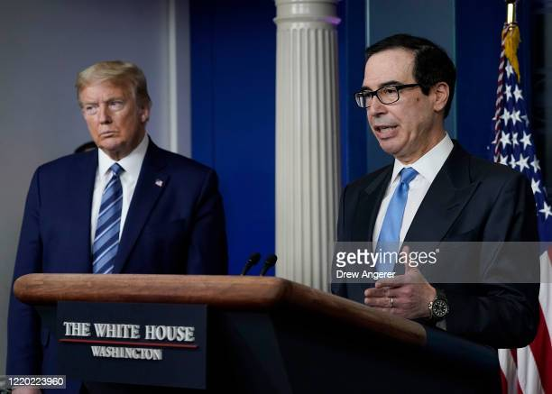 Treasury Secretary Steven Mnuchin speaks as US President Donald Trump looks on during the daily coronavirus task force briefing at the White House on...