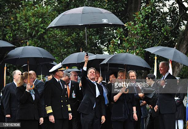 US Treasury Secretary Tim Geithner holds up his umbrella during an arrival ceremony for South Korean President Lee Myungbak on the South Lawn of the...