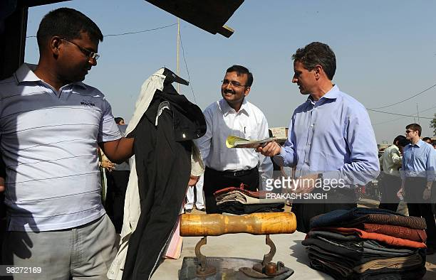 US Treasury Secretary Timothy Geithner talks with Indian laundry stall worker Mohammad Yacub at his roadside ironing stall as Abhishek Sinha the CEO...