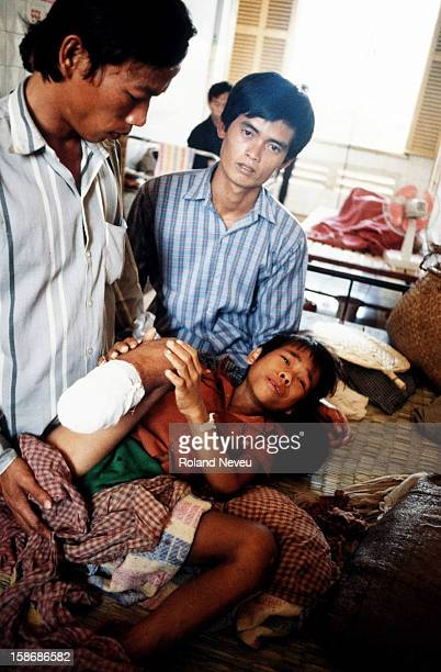 Treating a boy who has stepped on a landmine in a city hospital of Phnom Penh