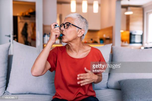 treatment during an asthma attack - asthma inhaler stock pictures, royalty-free photos & images