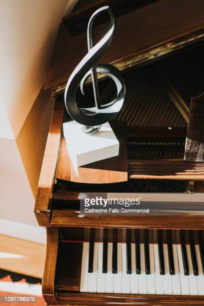 treble clef on a piano - symbolism stock pictures, royalty-free photos & images