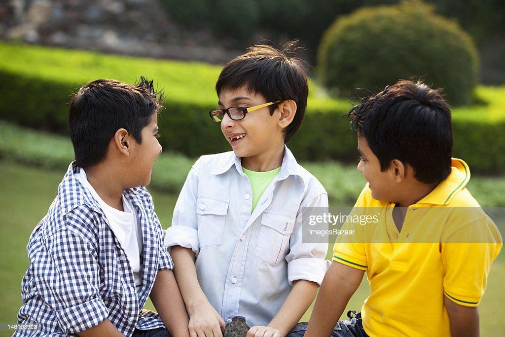 Tree boys (6-7) talking in park : Stock Photo