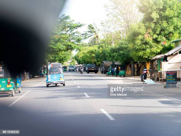 Tree lined street with a variety of businesses in Arugam Bay shot from the back of a motor bike
