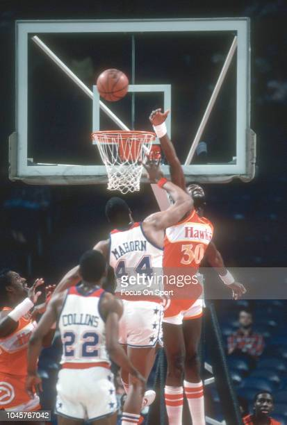 Tree Rollins of the Atlanta Hawks leaps to defend the shot of Rick Mahorn of the Washington Bullets during an NBA basketball game circa 1982 at the...
