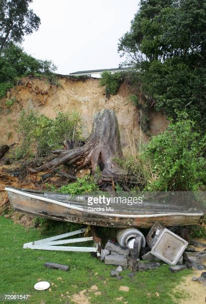 A tree stump which slid down an embankment lies on a picnic table and boat after part of the cliff gave way at Beach Haven North Shore October 02...