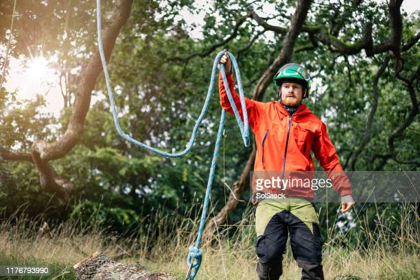 tree surgeon in woods wearing safety helmet holding blue rope - jacket stock pictures, royalty-free photos & images