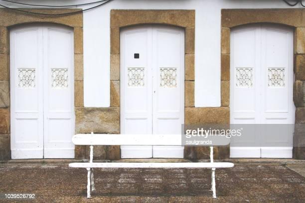 tree white doors with a bench - banco asiento fotografías e imágenes de stock