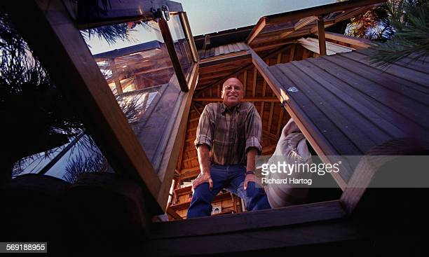 Treehouse builder Mike Chiavetta is all smiles as he looks down and out of his creation onto the ladder that leads up the tree and to the door of his...