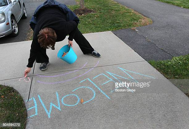 Treehouse Community founder Judy Cockerton writes a welcome sign with sidewalk chalk outside the community center Cockerton who has been nationally...