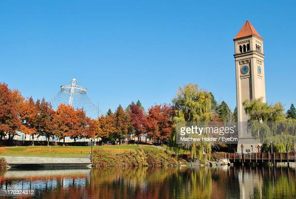 trees and building at waterfront against clear blue sky - spokane stock pictures, royalty-free photos & images