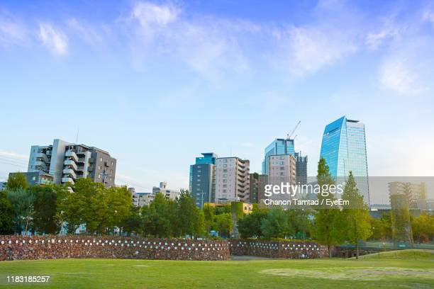 trees and buildings against blue sky - nagoya stock pictures, royalty-free photos & images