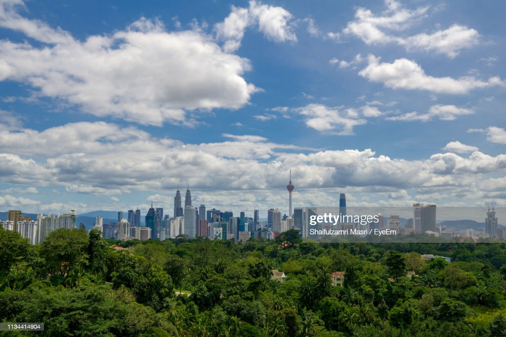 Trees And Buildings Against Cloudy Sky During Sunny Day : Stock Photo