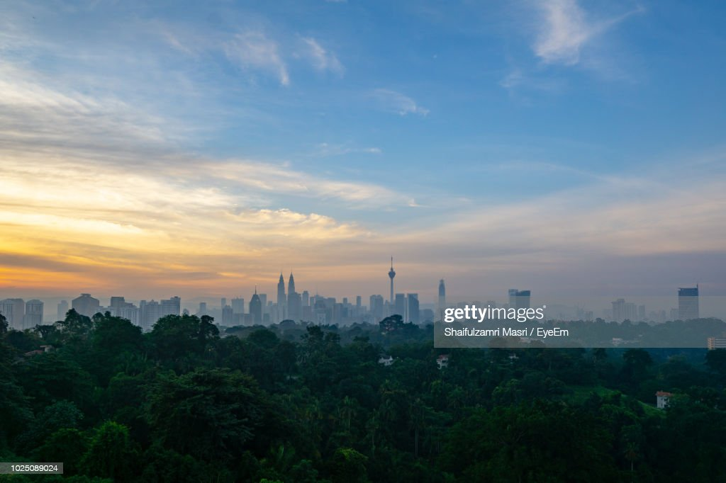 Trees And Buildings Against Sky During Sunset In City : Stock Photo