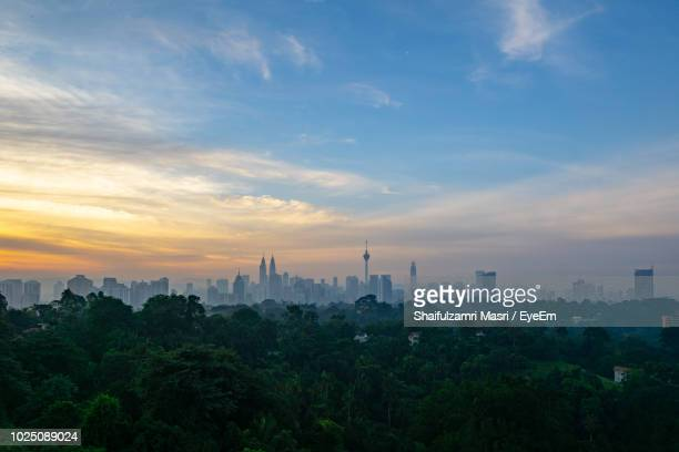 trees and buildings against sky during sunset in city - shaifulzamri stock pictures, royalty-free photos & images