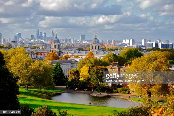 trees and buildings in city against cloudy sky - greenwich london stock pictures, royalty-free photos & images
