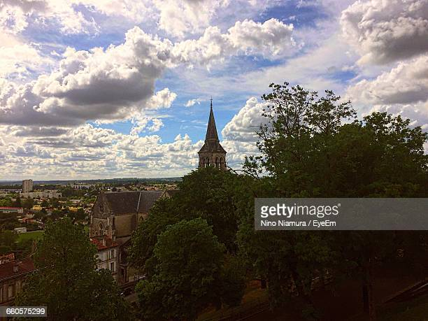 Trees And Church Against Cloudy Sky