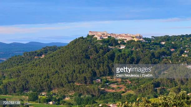 trees and houses in sea against cloudy sky - bandol photos et images de collection