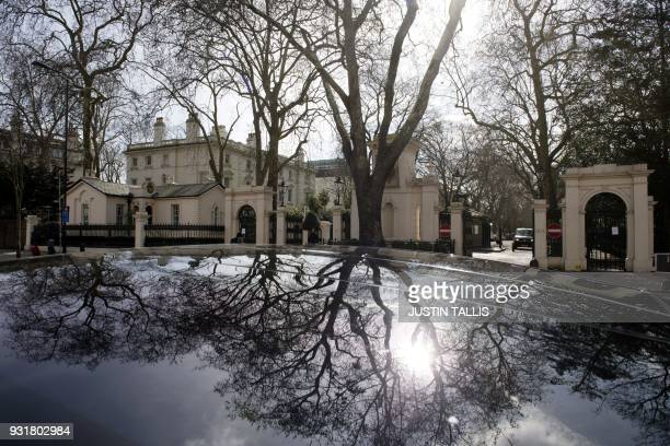 Trees are reflected on the roof of a car parked in front of a private road where The Russian Embassy is located in London on March 14 2018 / AFP...