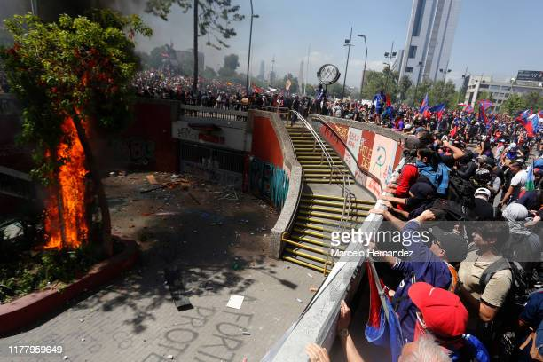 Trees burn as demonstrators wave flags during the seventh day of protests against President Sebastian Piñera on October 24 2019 in Santiago Chile...
