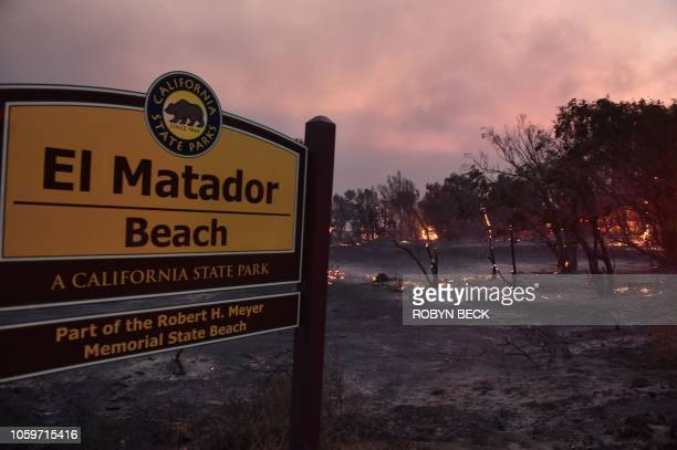 Trees burn at the entrance to El Matador Beach during the Woolsey Fire on November 9, 2018 in Malibu, California. - About 75,000 homes have been...