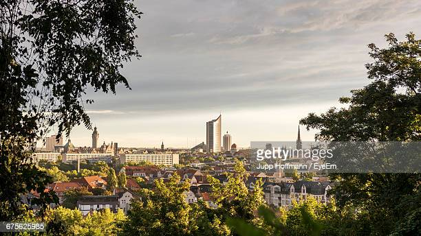 trees by cityscape against sky - leipzig saxony stock pictures, royalty-free photos & images
