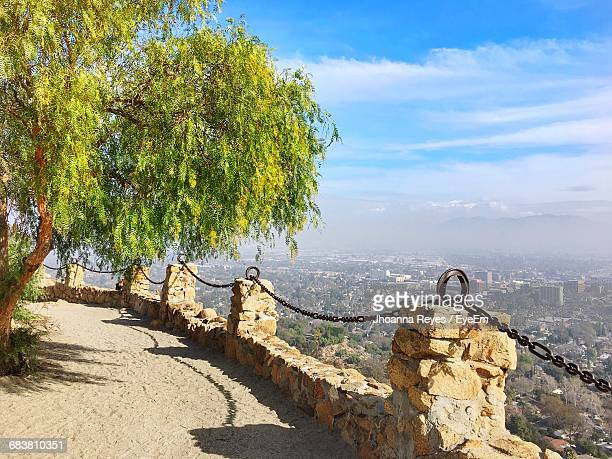 Trees By Fence At Mount Rubidoux Against Cloudy Sky During Sunny Day