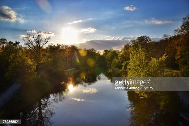 trees by river against sky during sunset - anfang stock pictures, royalty-free photos & images