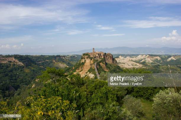 trees on landscape against sky - civita di bagnoregio foto e immagini stock
