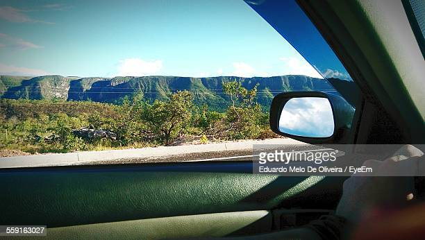 Trees On Landscape Near Mountains Seen Through Car Window