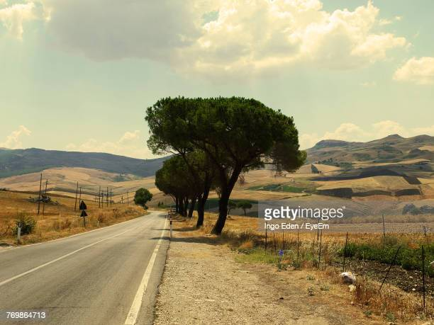 Trees On Road By Landscape Against Sky