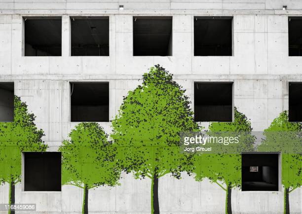 trees painted on unfinished concrete building - sustainable architecture stock pictures, royalty-free photos & images