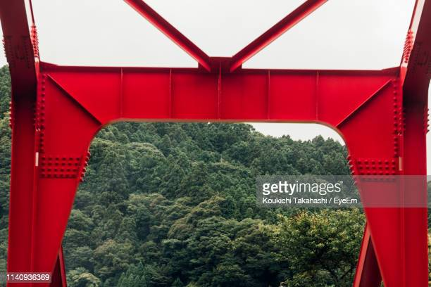 Trees Seen Through Red Bridge In Forest Against Sky
