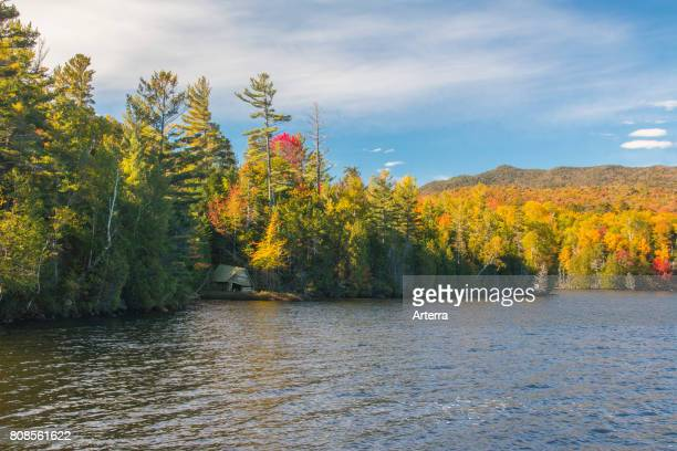 Trees showing autumn colours and old boathouse along Elk Lake in the Adirondack Park part of New York's Forest Preserve in Upstate New York USA