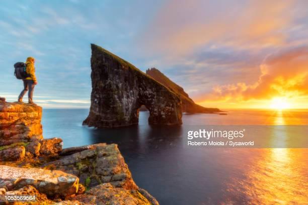 trekker admires drangarnir rock, faroe islands - デンマーク ストックフォトと画像