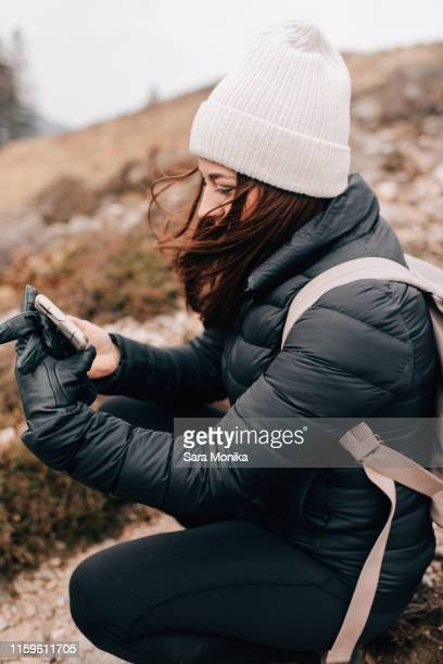 trekker kneeling to take selfie, trossachs national park, canada - padded jacket stock pictures, royalty-free photos & images