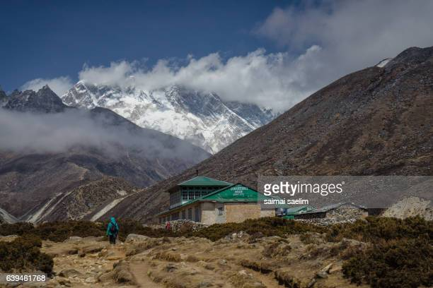 Trekker on the way to Everest base camp, with mountain and cloud in the background
