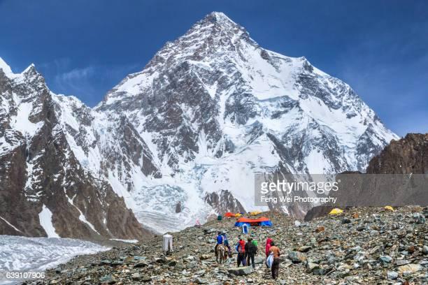 Trekker & Porter Walking Towards Broad Peak Base Camp With K2 In Background, Central Karakoram National Park, Gilgit-Baltistan, Pakistan