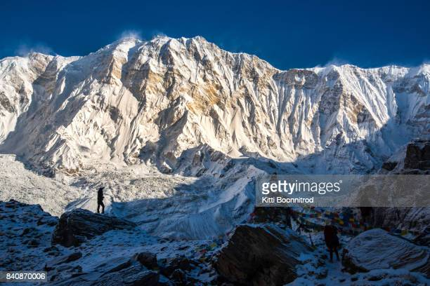 a trekker standing in front of annapurna south in the morning in nepal - annapurna conservation area stock photos and pictures