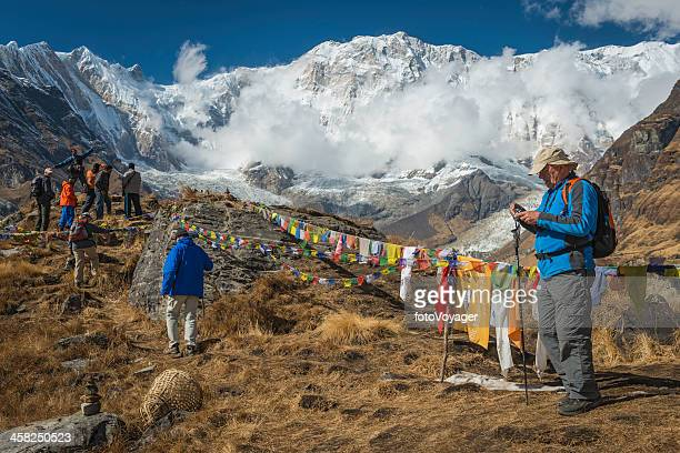 trekkers at annapurna base camp under mountain peaks himalayas nepal - annapurna circuit stock photos and pictures
