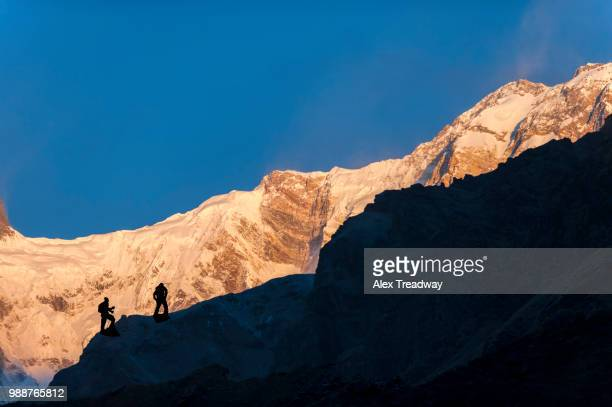 trekkers climb to the top of the lateral moraine beside the annapurna glacier to get a better view of annapurna 1, nepal, himalayas, asia - vista lateral bildbanksfoton och bilder