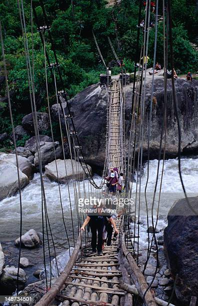 Trekkers crossing the suspension bridge over the Khudi Khola (river) and Khudi village (830m) in the Annapurna Circuit trek.