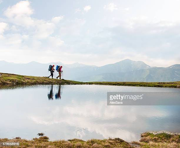 Trekkers passing by a calm lake in the mountains