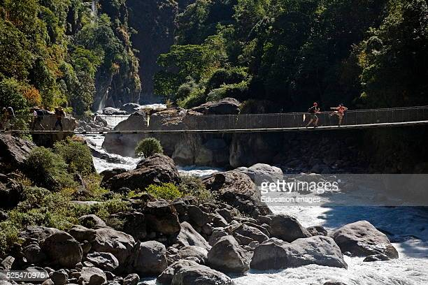 Trekkers Play Around On A Foot Bridge Over The Marsyandi River On The Annapurna Circuit East Of Jagat Nepal Himalaya