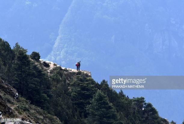 Trekkers walk along a path in the Everest region, some 140 km northeast of Kathmandu, on May 27, 2019. - Ten people have died in little more than two...