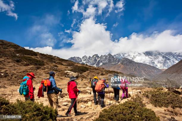 trekkers walk to final destination - everest base camp. - nepal stock pictures, royalty-free photos & images