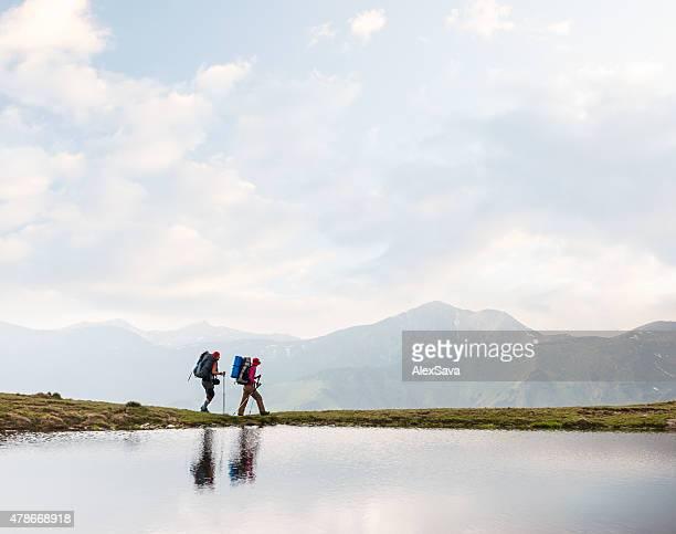 Wanderer zu Fuß in einem clear lake in den Bergen